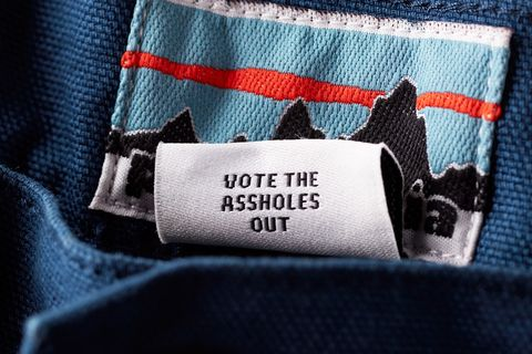 "a patagonia tag with the phrase ""vote the assholes out"""