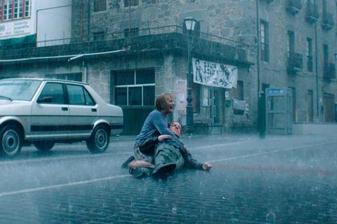 una mujer sostiene a un hombre muerto bajo la lluvia en patria