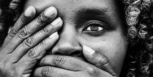 Keniaas meisje in zwart en wit, met haar handen voor haar mond.