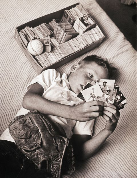 Boy Lying on Bed Studying Baseball Cards