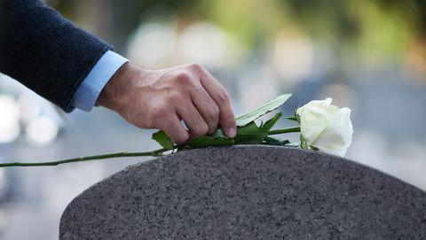 Man legt roos op grafsteen