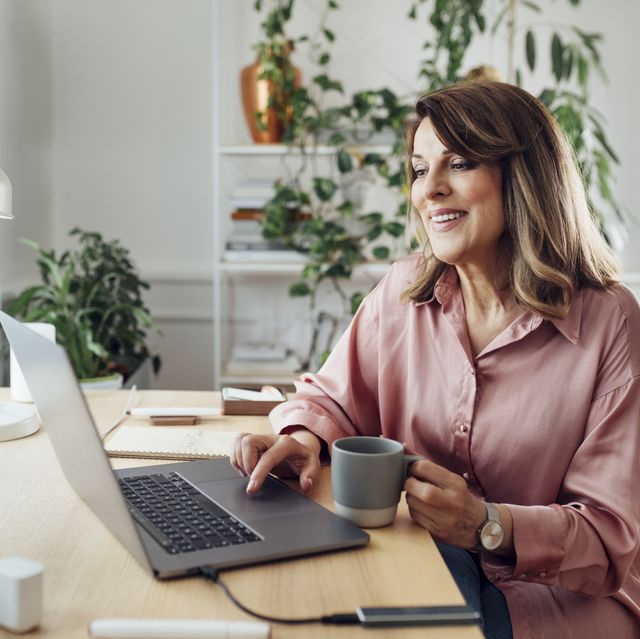 beautiful smiling mature woman sitting in the comfot of her home office and working, social distancing concept