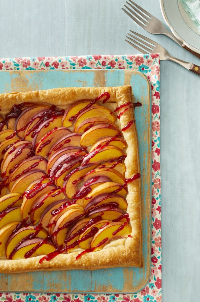 peach melba tart on blue wood surface forks on top right