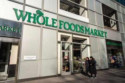 Pedestrians walk past an american multinational supermarket...