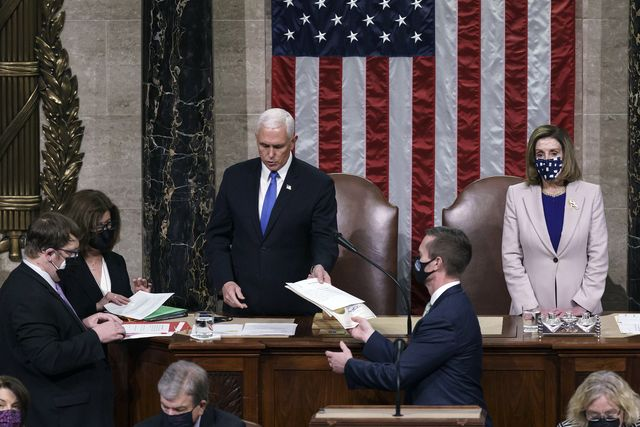 vice president mike pence hands the west virginia certification to staff as speaker of the house nancy pelosi, d calif, listen during a joint session of congress after working through the night, at the capitol in washington, thursday, jan 7, 2021 violent protesters loyal to president donald trump stormed the capitol wednesday, disrupting the process ap photoj scott applewhite, pool