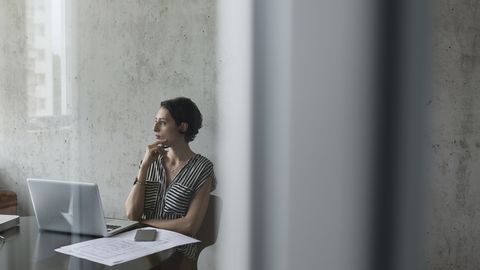 Pensive female architect at laptop looking away in conference room