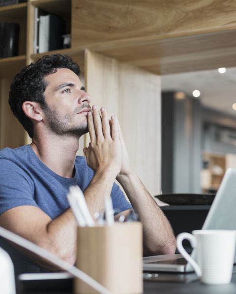 Pensive man at laptop in home office