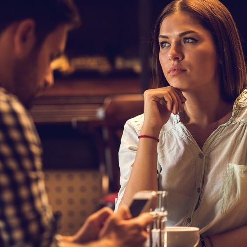 Pensive woman thinking while sitting in cafe with her boyfriend.