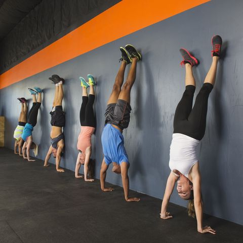 People doing handstands together in gym