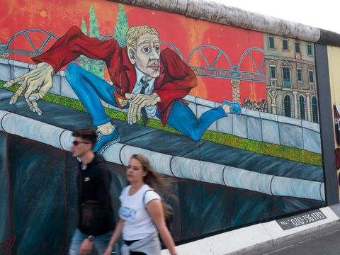 People seen next to the remains of the wall that were...