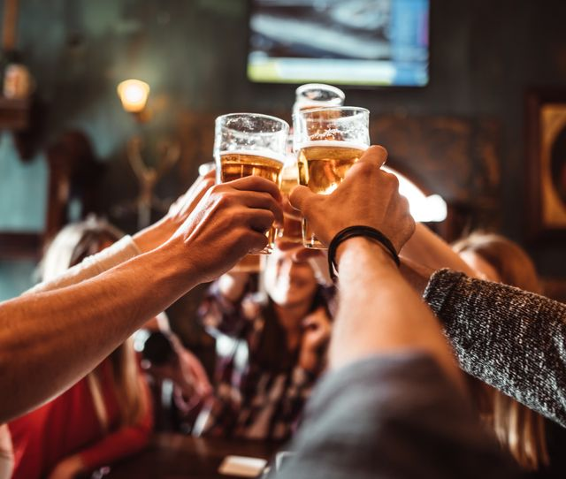 people talking and toasting in a pub with the beers
