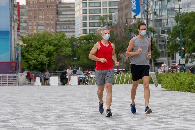 dos corredores con mascarilla por nueva york durante la pandemia de la covid 19