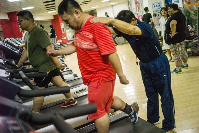 varias personas con sobrepeso entrenan en un gimnasio chino