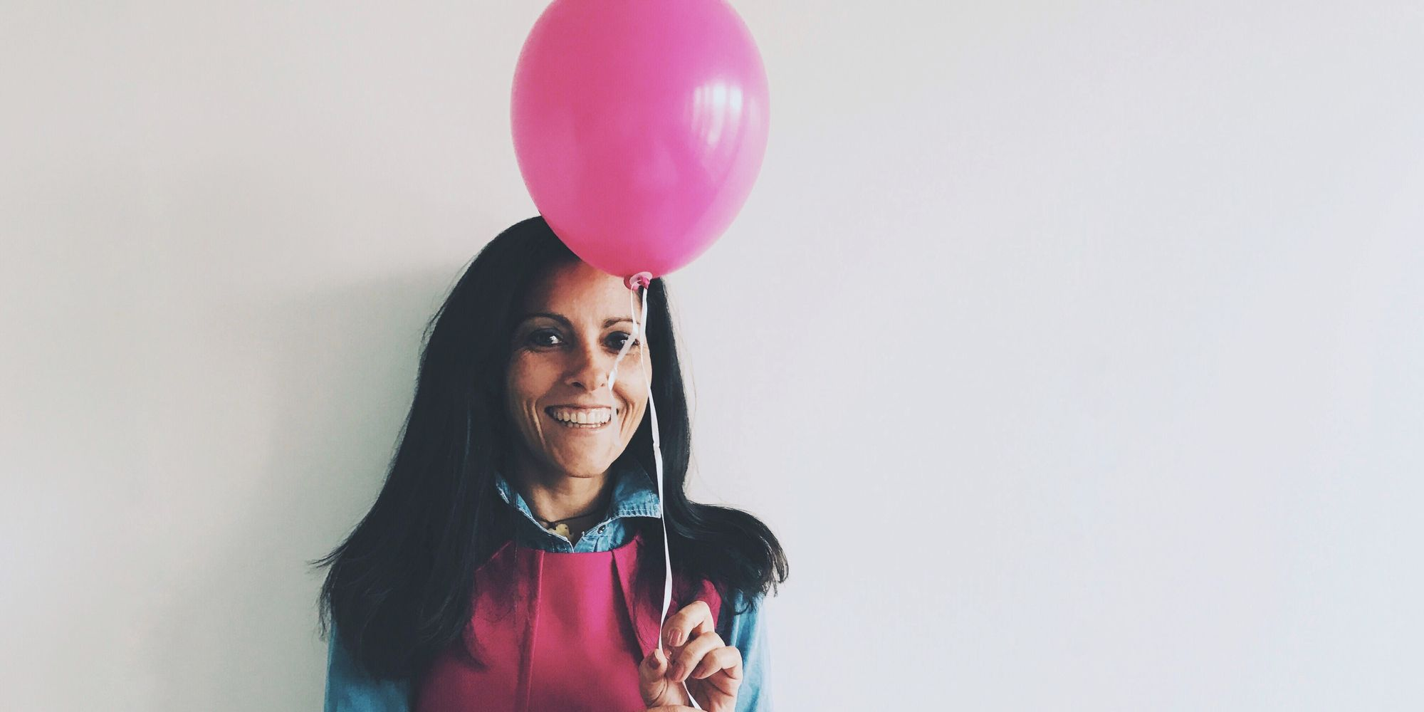 Portrait Of Woman With Pink Balloon Against White Background