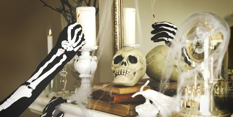 Person dressed in a skeleton costume lights a candles. Halloween composition on fireplace