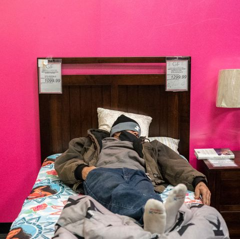 a man in a beanie takes a nap on a wooden bed at gallery furniture store in houston, which transformed into a warming station and opened its doors to cold texans who lost power