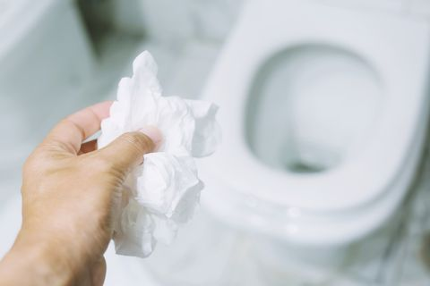 close up hand holding a tissue to be thrown into the toilet bowl can not drain water of toilet paper in the toilet bowl cause the stool to clog up