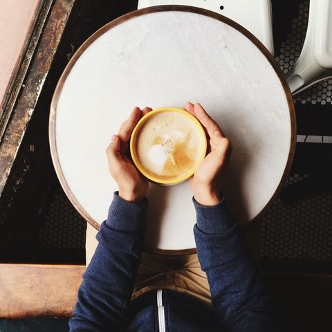 Personal perspective of a man holding cappuccino bowl with two hands