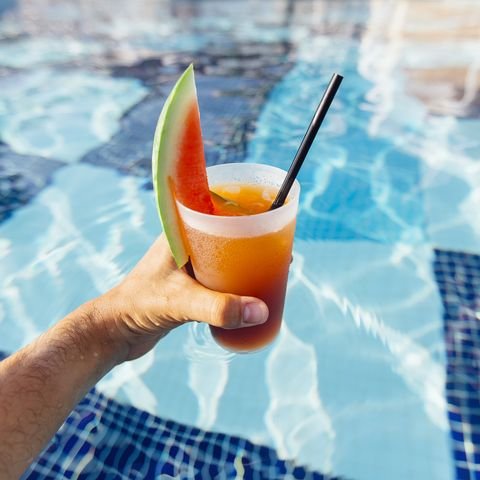 personal perspective view of drinking watermelon cocktail in swimming pool