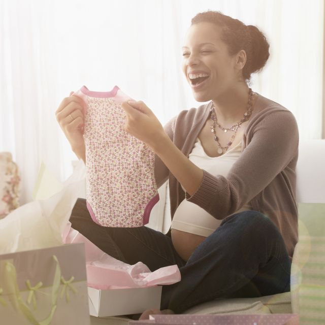 Pregnant mixed race woman opening gifts at baby shower