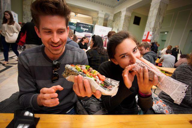 dos jóvenes comen en un festival de comida en polonia