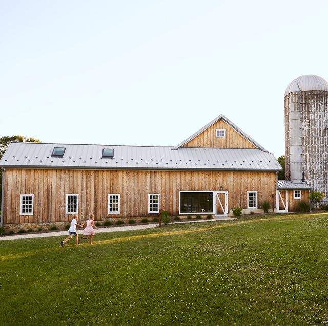 a modern wooden barn with two kids running outside