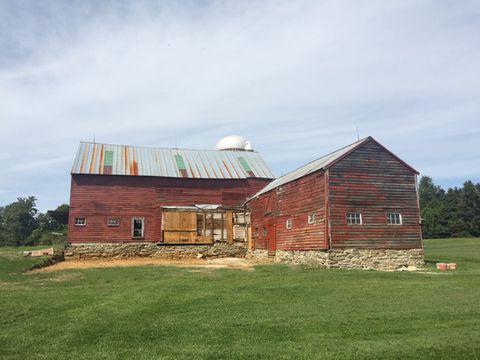 the back of an old red barn in a field of green grass