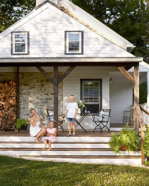 a mom and a boy and girl sit on the porch steps of a country house