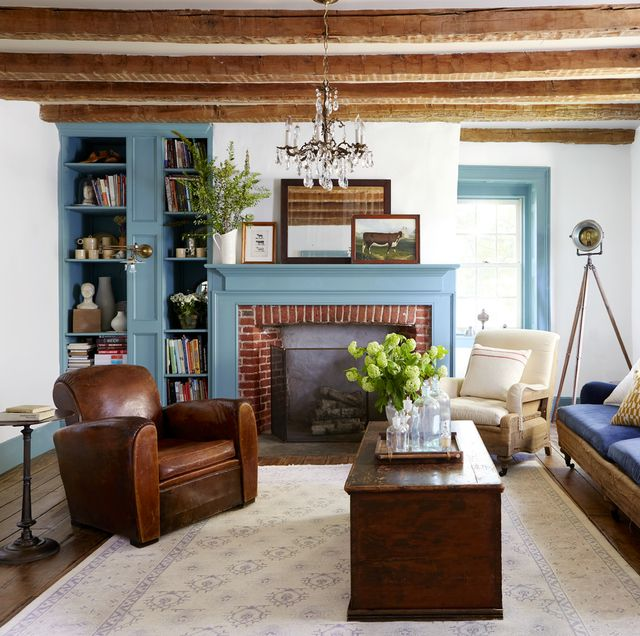 white walls wooden ceiling beams and blue painted trim in a living room with a fireplace