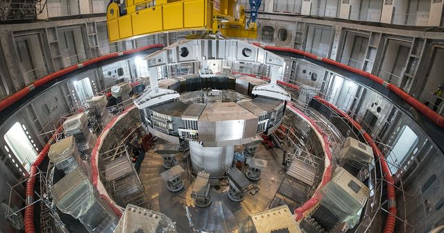this photo shows the installation of the first superconducting magnet, poloidal field coil number 6, in the tokamak pit at the iter construction site