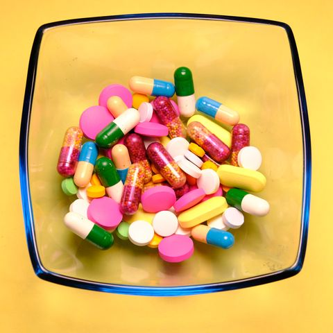 pharmaceutical medicine pills, tablets and capsules in bowl on yellow background