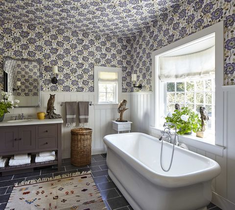 the upper walls and ceiling are covered in a flowery  wallpaper and there is a soaking tub under the window