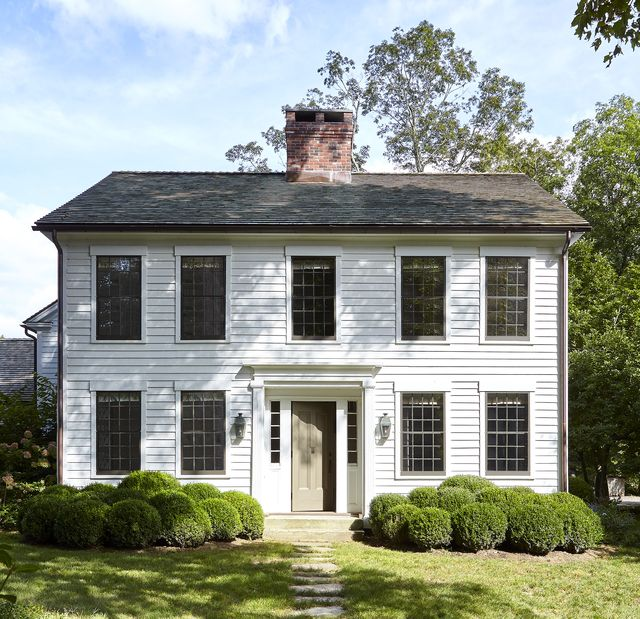 the restored facade reflects its original design including a side gabled roof central chimney and door sidelights