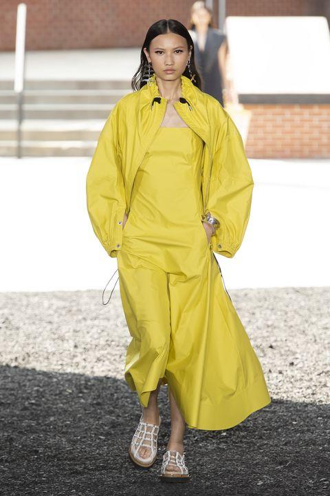 Clothing, Yellow, Fashion model, Fashion, Raincoat, Outerwear, Street fashion, Fashion design, Overcoat, Fashion show,