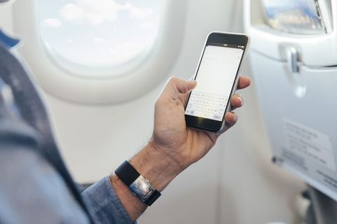 Man sitting on an airplane holding smartphone