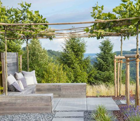 built in wooden bench under pergola, stone mulch, stepping stone path