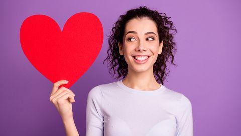 vrouw met zwarte krullen is heel verliefd en houdt een papieren hartje vast