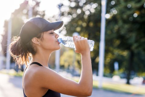sporty young woman drinking water