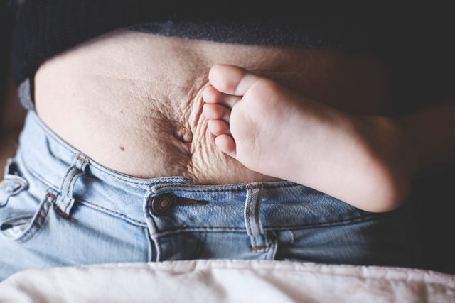 a womans belly after giving birth next to the barefoot of her son