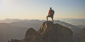 Photograph of adventurous backpacker standing on mountain peak, North Cascades National Park, Washington State, USA