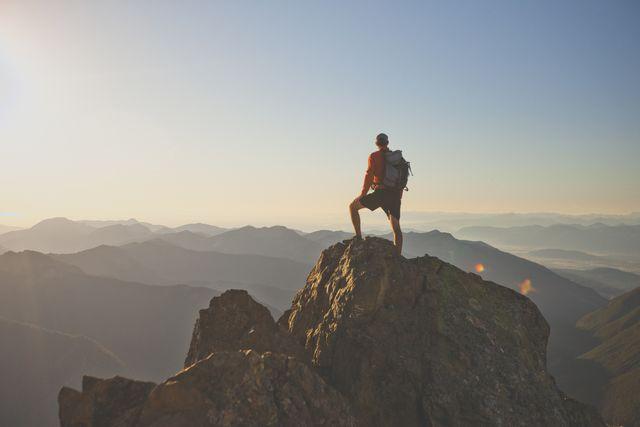 adventurous backpacker standing on mountain peak, north cascades national park, washington state, usa