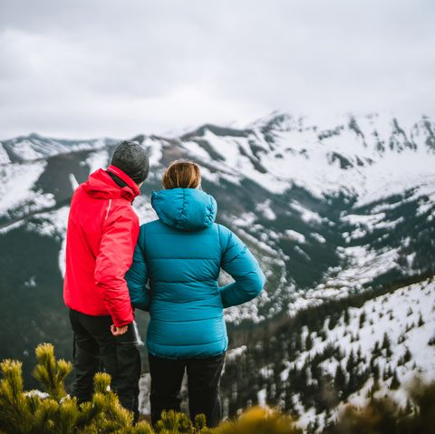 photographer shares ideas with woman on mountain in winter