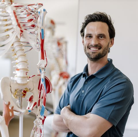 physiotherapist standing by anatomical skeleton with arms crossed
