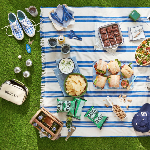 a picnic setup with bocce ball, sandwiches, and a blue and white blanket