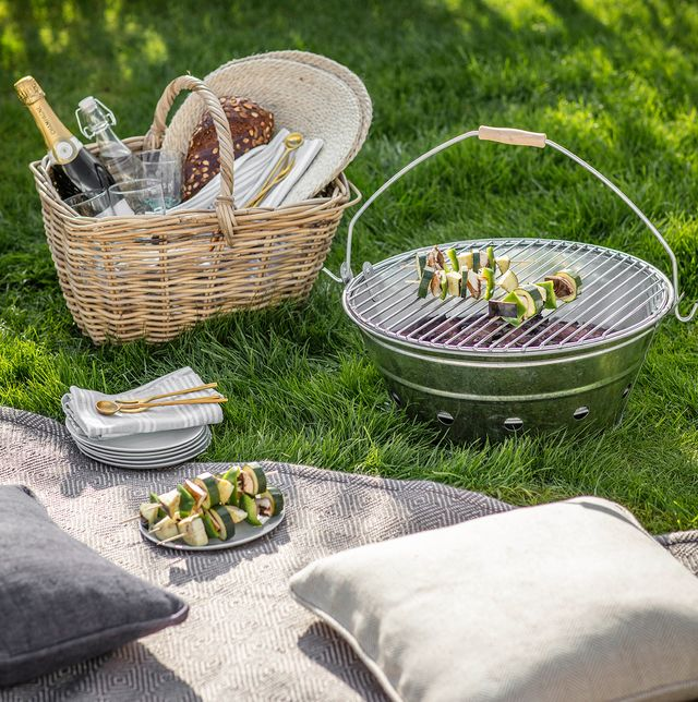 barbacoa portátil y cesta de mimbre en un picnic