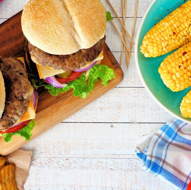 Picnic scene with hamburgers, corn and potato wedges