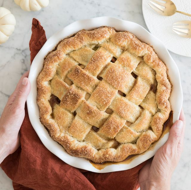 hands holding baked pie in dish