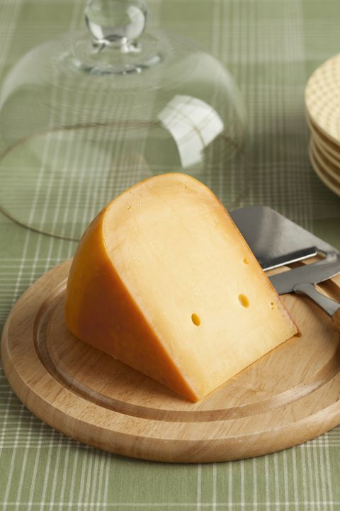 Piece of Dutch Gouda cheese on a wooden board