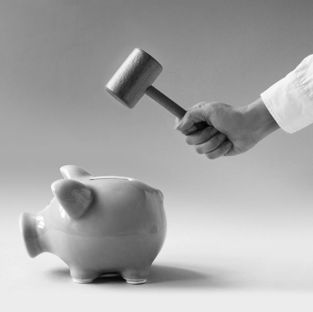 women hand using hammer trying to break a pink colour piggy bank on blue background