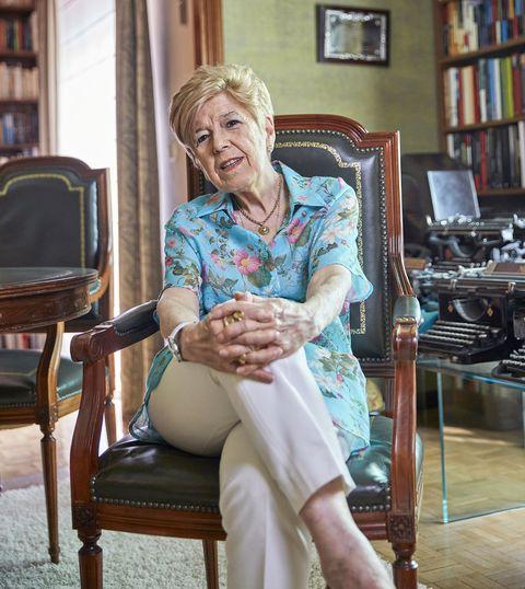 la escritora posa, con una camisa de flores y pantalón beige, en uno de los sillones de su casa